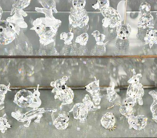 Une vitrine en verre, ainsi qu'un groupe de figures d'animaux en cristal Swarovs…