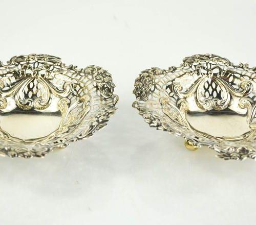 Une paire de plats en argent, percés et estampés de décorations, et reposant sur…