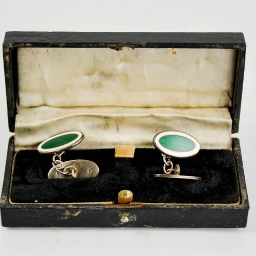 Une paire de boutons de manchette de forme ovale en argent et émail vert, dans u…