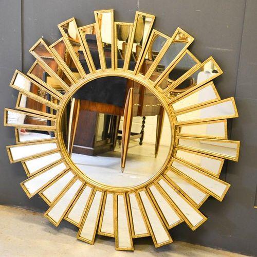 Un miroir étoilé en bois doré, dans le style Art Déco, le centre en forme de ron…