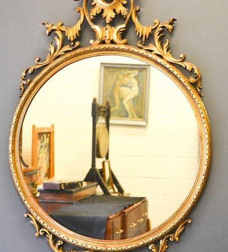 Un miroir mural doré, le miroir circulaire avec le sommet crêté, 107cm de haut.