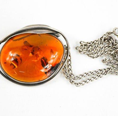 Un collier pendentif en argent et ambre, l'ambre mesure 4½cm de long.