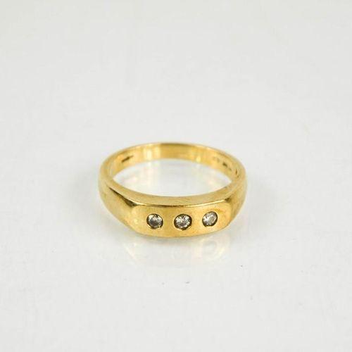 Une bague à trois pierres en or 9ct et diamants, taille U/V, 5.1g.