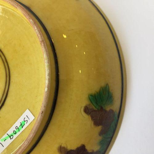 Soucoupe chinoise à fond jaune, aubergine et vert, marque Kangxi et de l'époque,…