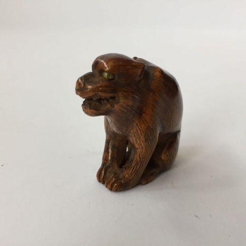 Un netsuke japonais en bois, 19ème siècle, sculpté comme un chien grognant avec …
