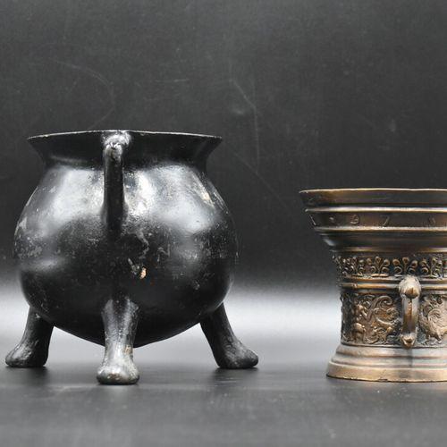 PILONS Un pilon en bronze ciselé, et un pot en fonte noire sur trépieds. Dimensi…