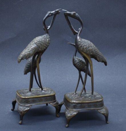 Paire de sculptures en bronze à figurant un échassier tenant un serpent dans son…