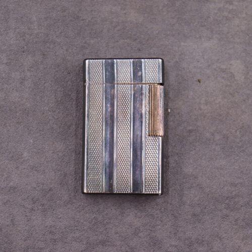 DUPONT DUPONT. Briquet en métal argenté guilloché, signé et numéroté au dessous.…