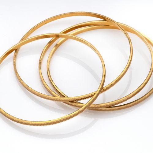 Four 20k gold bangles Quatre bracelets en or 20k, à décor de cannelures. Poids b…