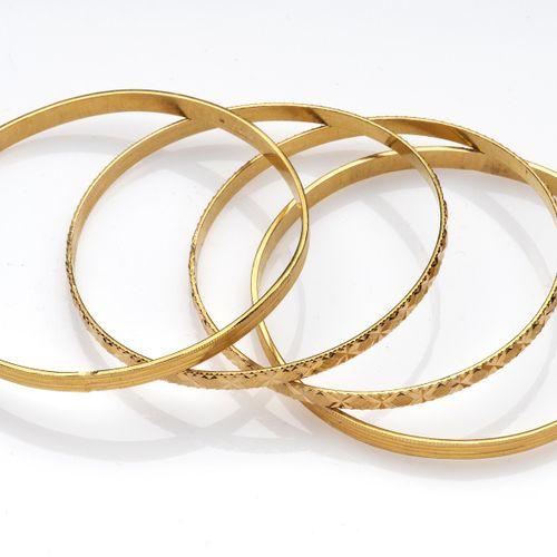Four 20k gold bangles Quatre bracelets en or 20k, Deux paires avec décorations d…