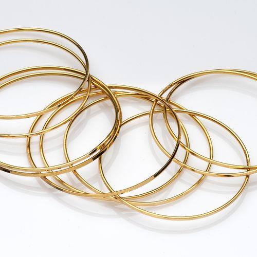 Ten 20k gold bangles Dix bracelets en or 20k, de forme filaire à facettes. Poids…