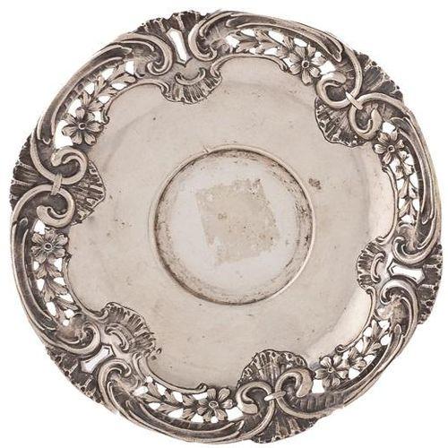 Piccolo piatto in argento decorato con volute e fiori. 14,5 x 14,5 cm Peso: 54 g…