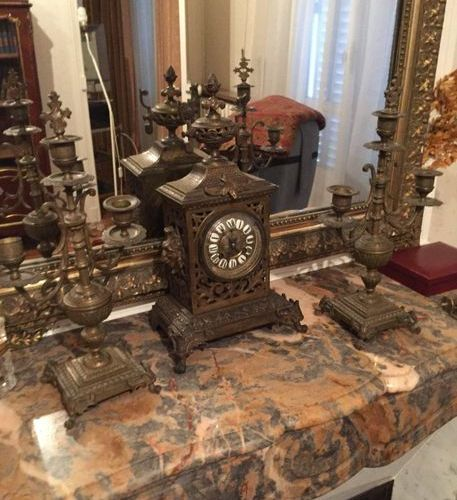 Antique metal mantelpiece with a clock and 2 torches