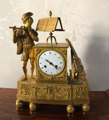 Clock in carved, chiselled and gilded bronze. Decoration of a troubadour with fl…