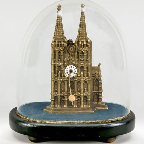 Small table clock under glass dome on wooden base, Cologne Cathedral in cast bra…