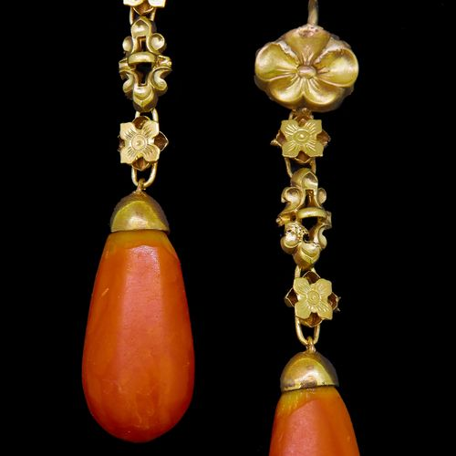 PAIR OF AMBER DROP EARRINGS, the top of floral relief design, suspending floral …