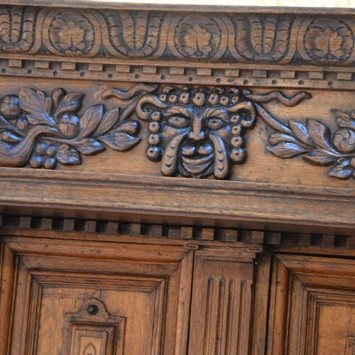 Important buffet en chêne sculpté et 浅色和深色的木质镶嵌,上部开有两扇门,下部有一个抽屉和两扇门,雕刻有脸部、花朵和奖杯的…