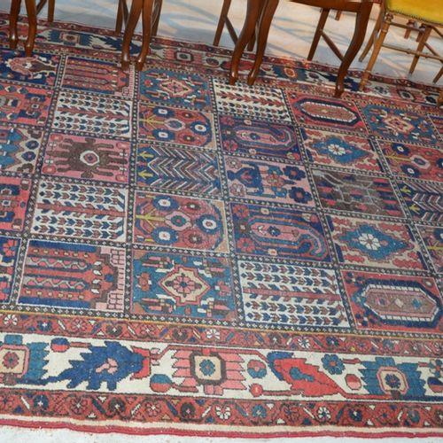 Un grand tapis à fond rouge à décor géométrique  320 x 210 cm  (Usures)