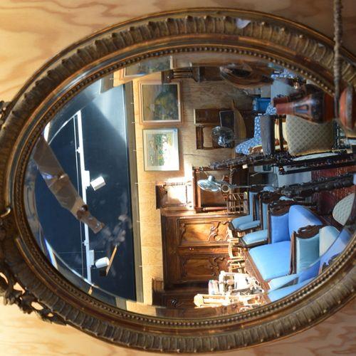 Miroir ovale en bois doré à décor de coquilles.  120 x 80 cm.  (En l'état)