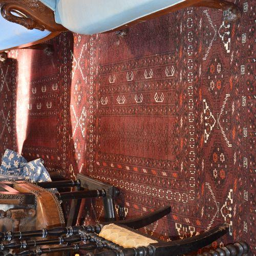 Un tapis a fond rouge à décor géométrique  260 x 190 cm