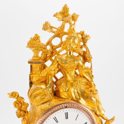 A ormolu gilt table clock made of bronze with a figurine of a lady and romantic …