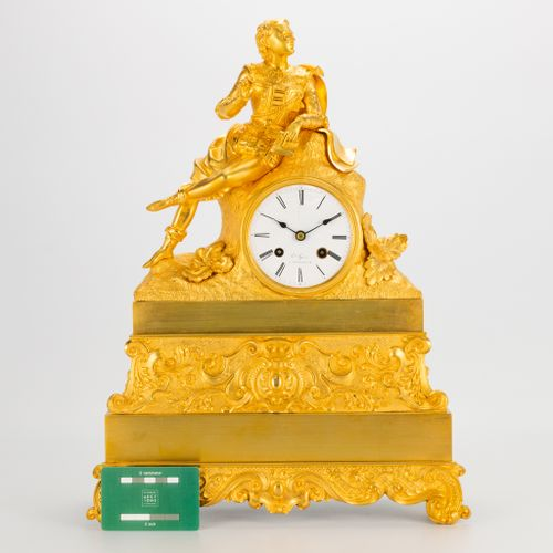 A ormolu gilt table clock made of bronze with a figurine of a noble man, enamel …