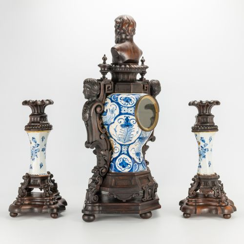 A sculptured wood mounted faience clock with candlesticks. Made in Delft, The Ne…