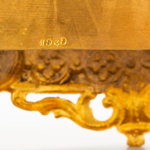 A ormolu gilt table clock made of bronze with a figurine of a lady and putti, en…