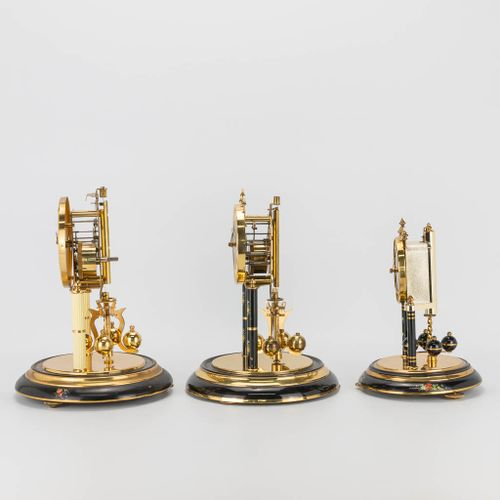 A collection of 3 table clocks under a glass dome, marked Kern and Hermle. (30 x…