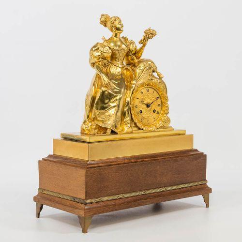 An ormolu gilt table clock on a wood base, with a female figurine holding flower…