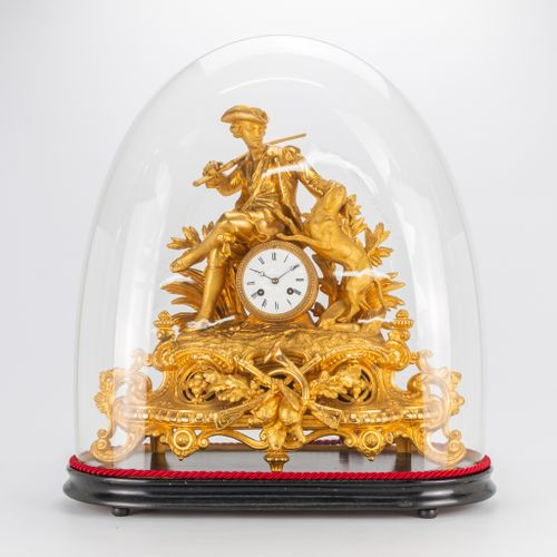 A spelter mantle clock, with a hunter figurine and his dog, hunting trophies. Un…