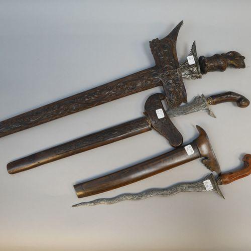 Ensemble de trois kriss malais.  Fourreaux et montures en bois, lames « flamboya…