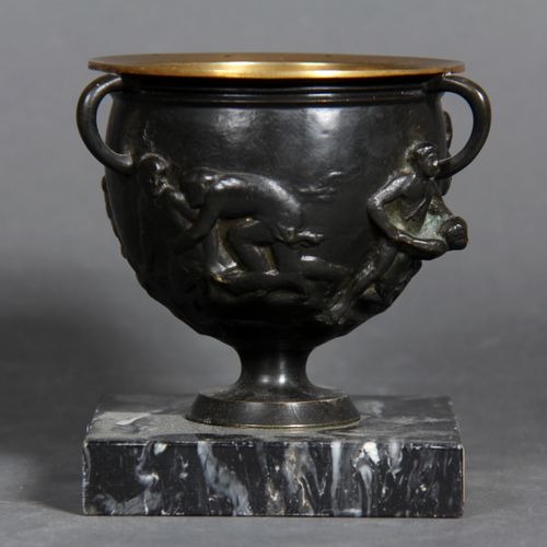 A black patina bronze bowl with three handles decorated with a wrestling scene. …