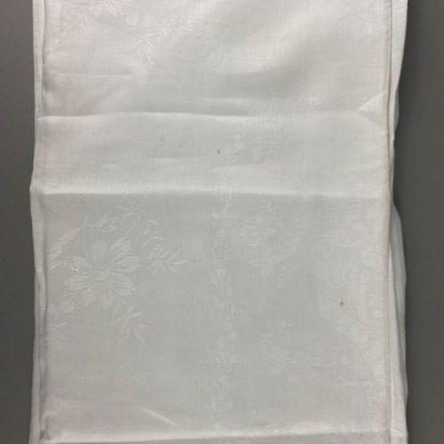 Grande nappe,  en coton damassé blanc à décor de végétaux et frise de ruban.  Do…