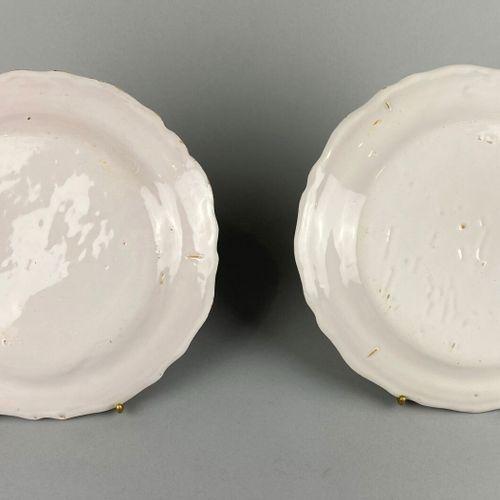 Moustiers。  两个陶制盘子,边缘有轮廓。  赭石色浮雕装饰的小丘上的怪人。  18世纪。  D 25和24.8厘米。  有一个细小的缺口和修复。