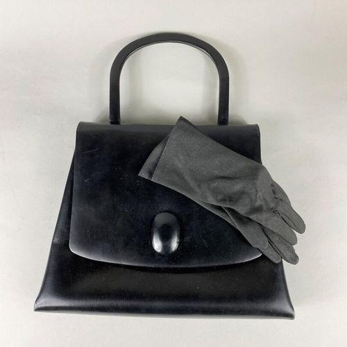 Sac à main vintage,  de forme trapézoïdale en cuir noir lisse.  Ouvrant par un a…