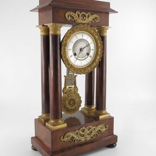 A French Charles X ormolu and flame mahogany portico clock, Empire style, signed…