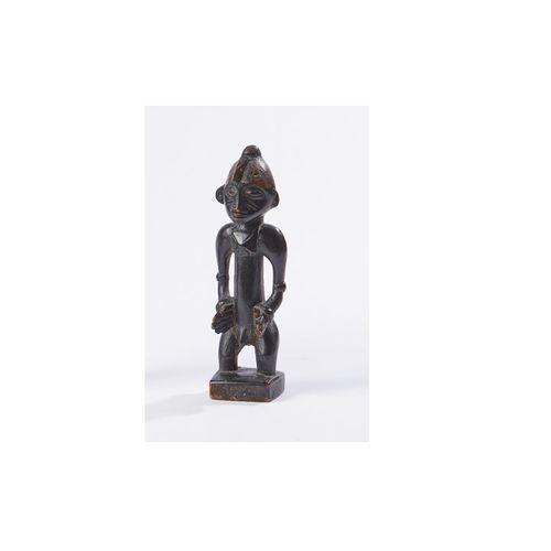 Personnage masculin en bois noirci représenté debout les mains sur les hanches. …