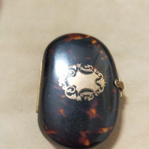 Porte monnaie ovale en écaille de tortue orné d'un cartouche doré. L'intérieur à…