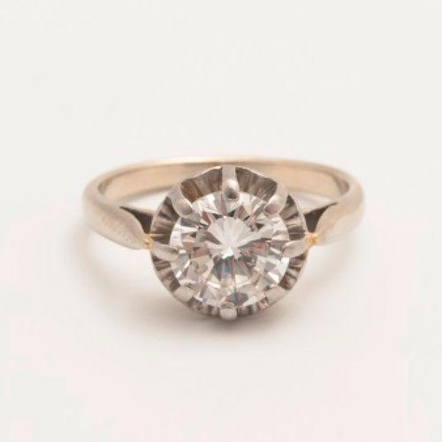 Solitaire en or blanc 18K (750 millièmes) serti clos d'un diamant taillé en bril…