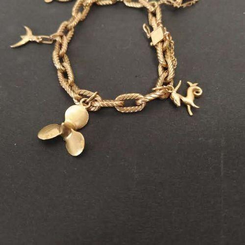 Bracelet souple en or jaune 18K, maille gourmette à cinq breloques  Poids : 40.4…