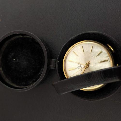 Pontifa. Petit réveil de voyage rond, en cuir noir et métal doré. Index bâtons. …