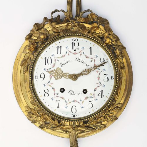 挂钟 巴黎,路易十六风格,Julien Béliard 圆形,阶梯状,部分镀金的青铜表壳,框架是多叶的藤蔓和花枝,有大的蝴蝶结冠。有花纹装饰的珐琅表盘,阿拉伯数…