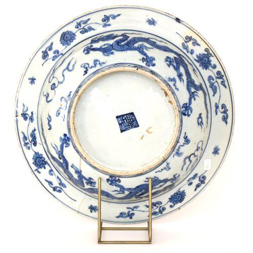 CHINE  PLAT en porcelaine bleue à décor central d'un dragon à quatre griffes vol…