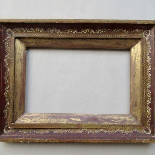 Cadre en bois mouluré doré au cuivre et peint rouge à décor gravé de rais de per…