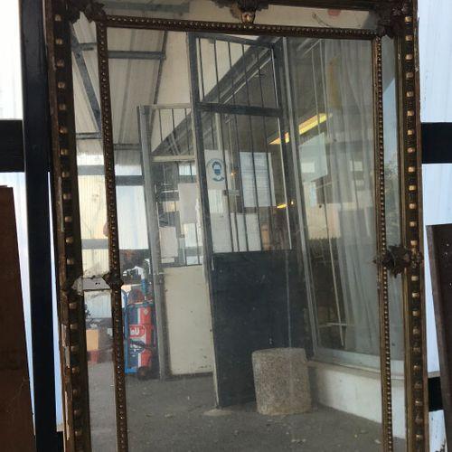 Grand miroir à pare closes en bois et stuc doré, le fronton orné d'un vase.  Epo…