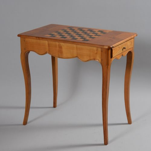 樱桃木游戏桌,凸形腿上开有一个抽屉,顶部镶嵌有棋盘格图案。  路易十五风格,20世纪  高72.5厘米,宽77厘米,深47.5厘米