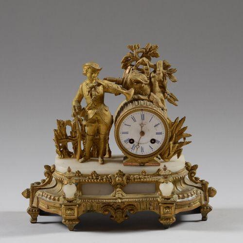 Pendule en régule doré et albâtre à décor d'un chasseur sonnant de la trompe.  F…