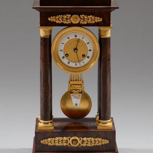 一个桃花心木贴面和镀金青铜的门廊钟,放在一个长方形的底座上,上面装饰着玫瑰花的门楣,支撑着四根柱子,框住机芯。  复原期  高度:45厘米  侧面有小的木皮事故
