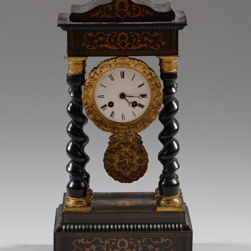 黑檀木饰面的门廊钟,镶嵌着浅色的木头,四根扭曲的柱子框住了鎏金的青铜机芯。  拿破仑三世时期  高度44厘米